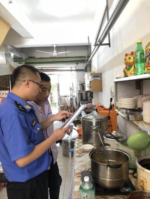 综合执法人员对餐饮企业进行油烟污染检查